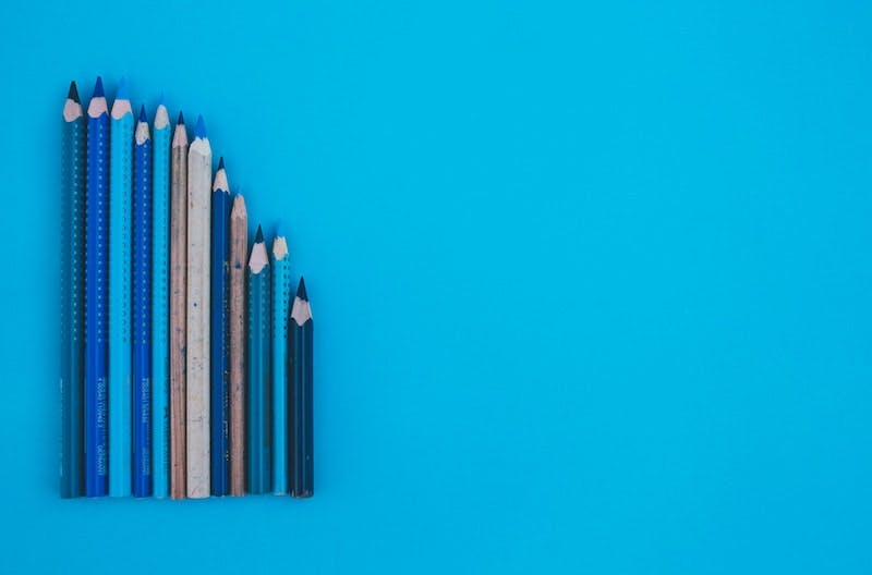 A mix of different sized pencils is laying on a blue surface