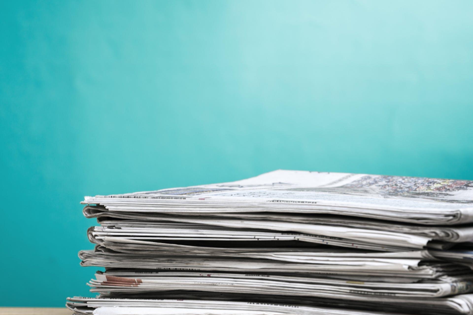 """Man sieht Zeitungen auf einem Stapel vor einem türkisen Hintergrund liegen. Das ist das Titelbild für unseren Beitrag: """"Eine erfolgreiche Pressemitteilung schreiben"""""""