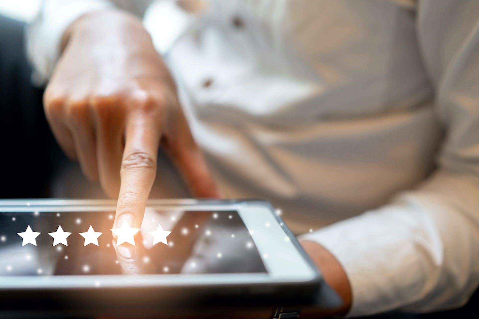 Foto von einem Mann, der auf seinem Tablet eine Sternebewertung abgibt, um eine manuelle Sentimentanalyse durchzuführen