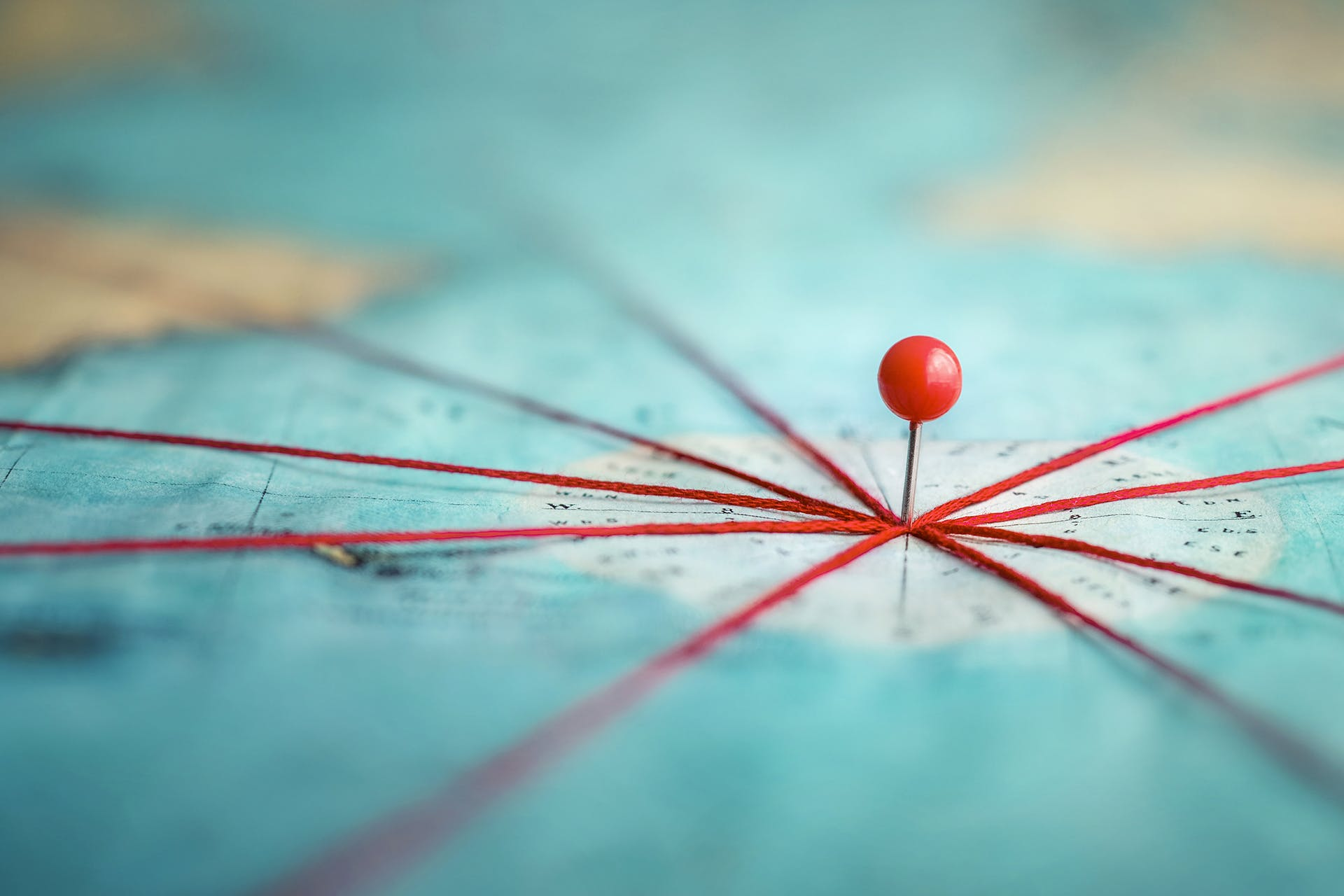 Map pin connecting several red threads. Header image for planning a marketing strategy for 2021 blog post.