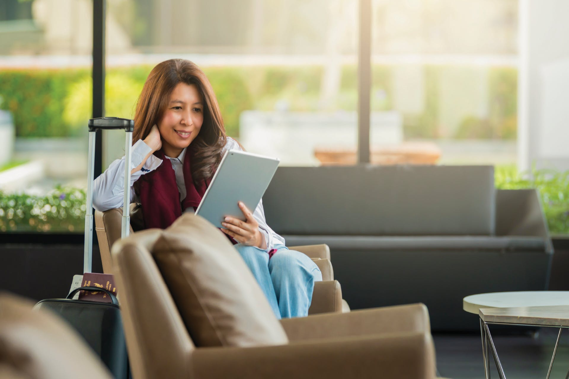 A woman using a tablet while sitting in a hotel lobby with her luggage