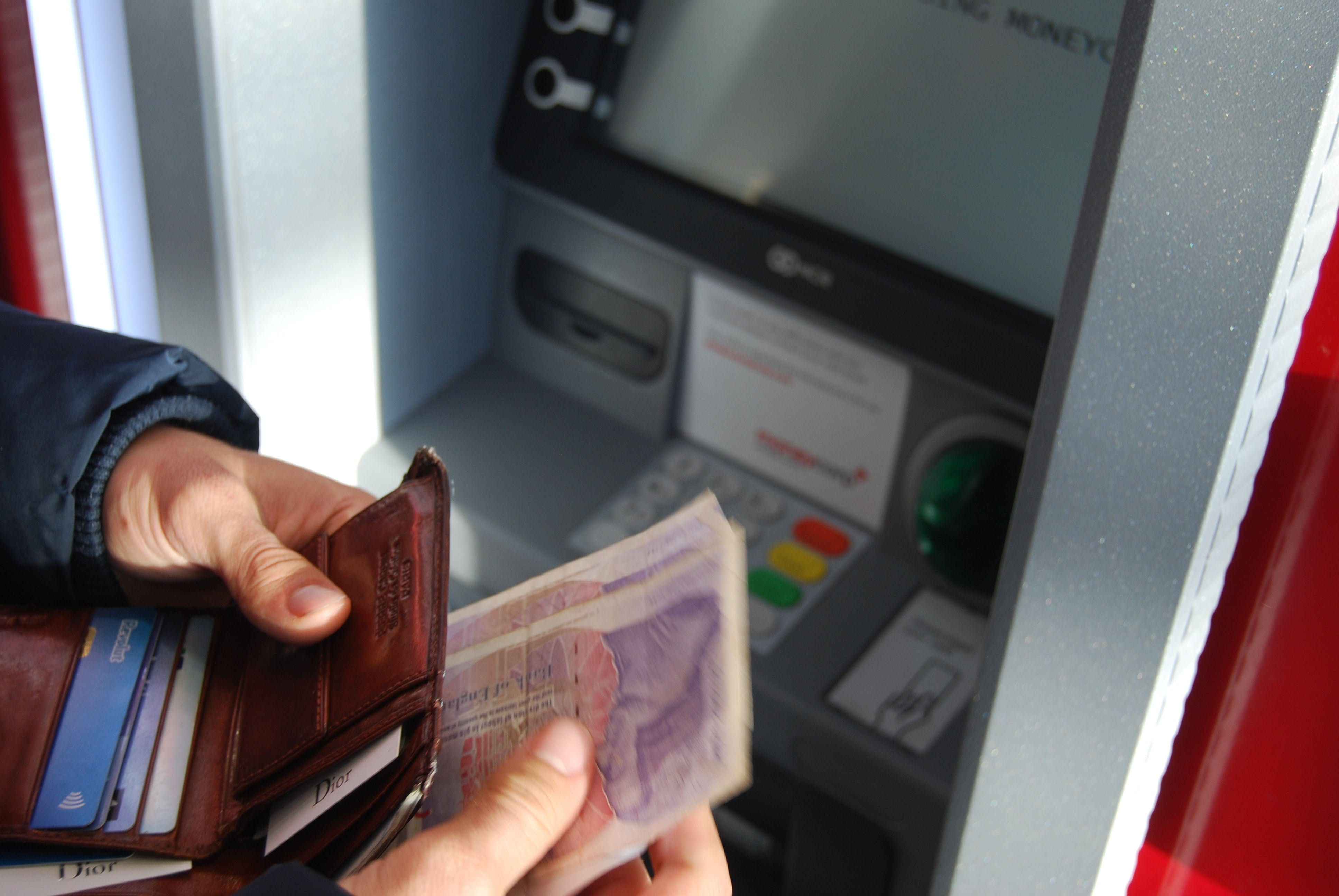 person at a bank atm with bank notes in a wallet