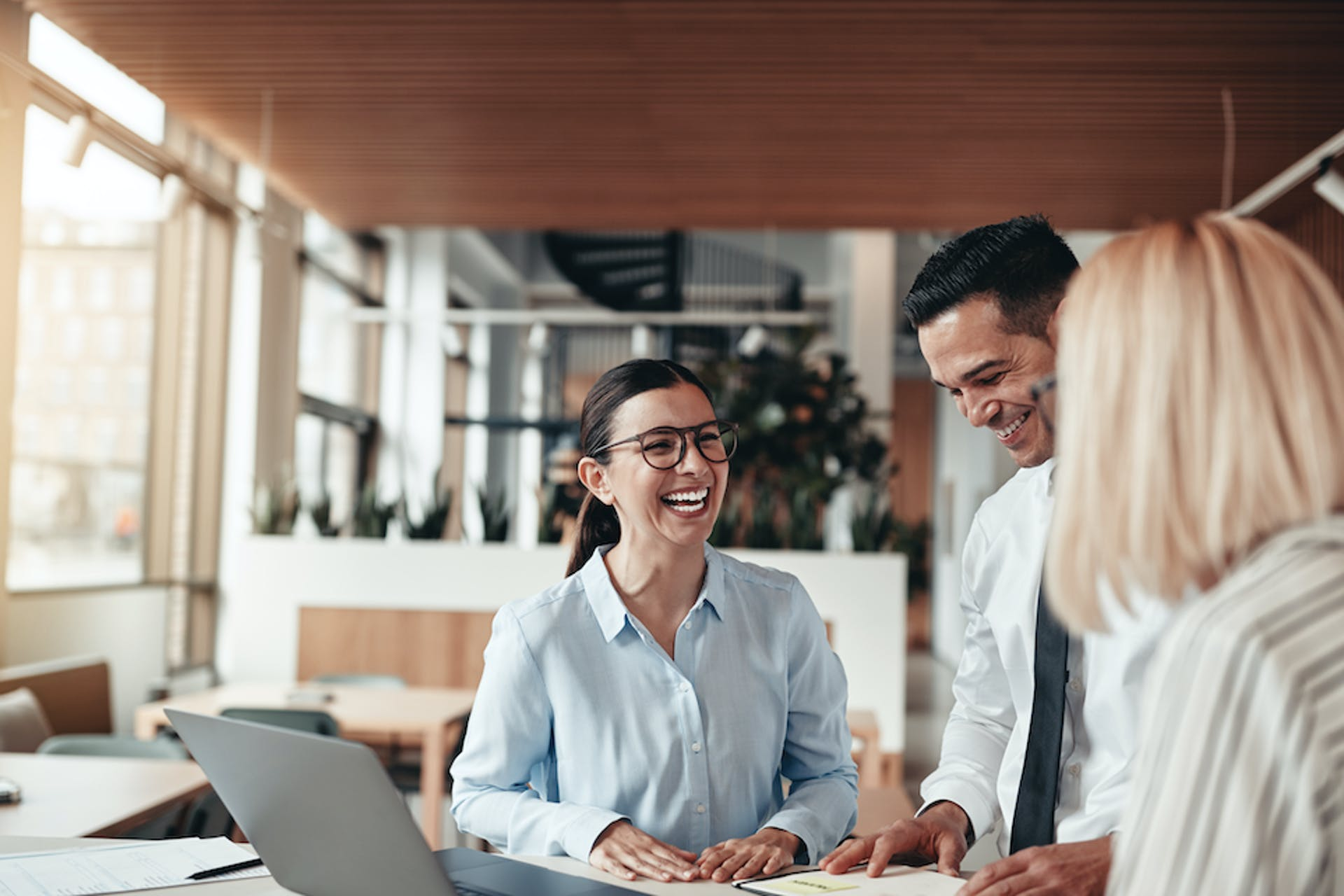 Drei Geschäftsleute lachend bei einer Besprechung