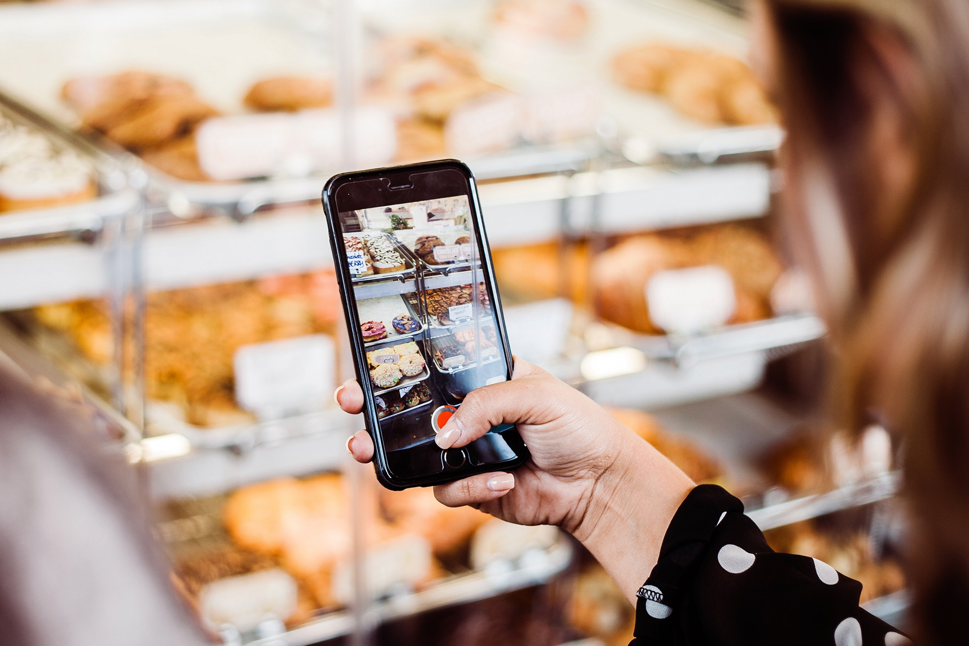 a woman using her phone to take a photo of pastries