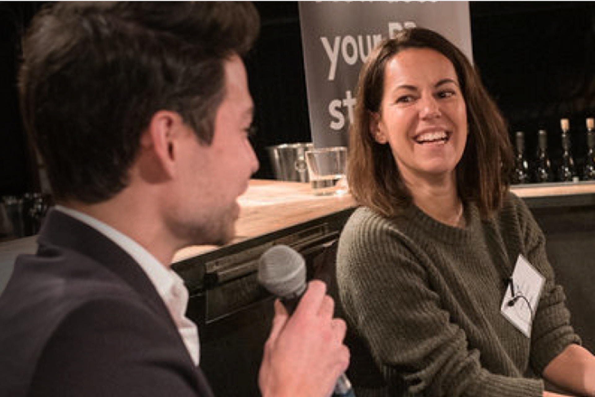 Man talking into a microphone and a woman looking at him, laughing.