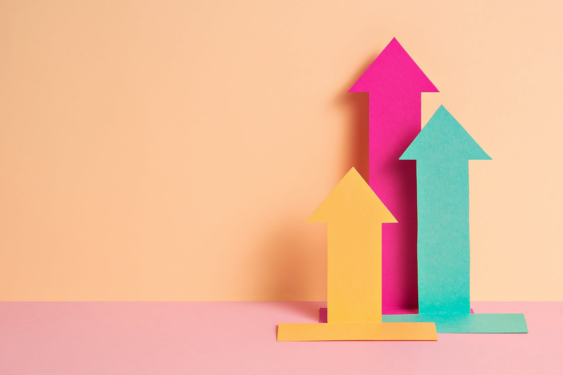 Three colorful arrows cut out of paper pointed upwards. The arrows are meant to reflect the direction of a graph that you might find after creating a PR or marketing report.
