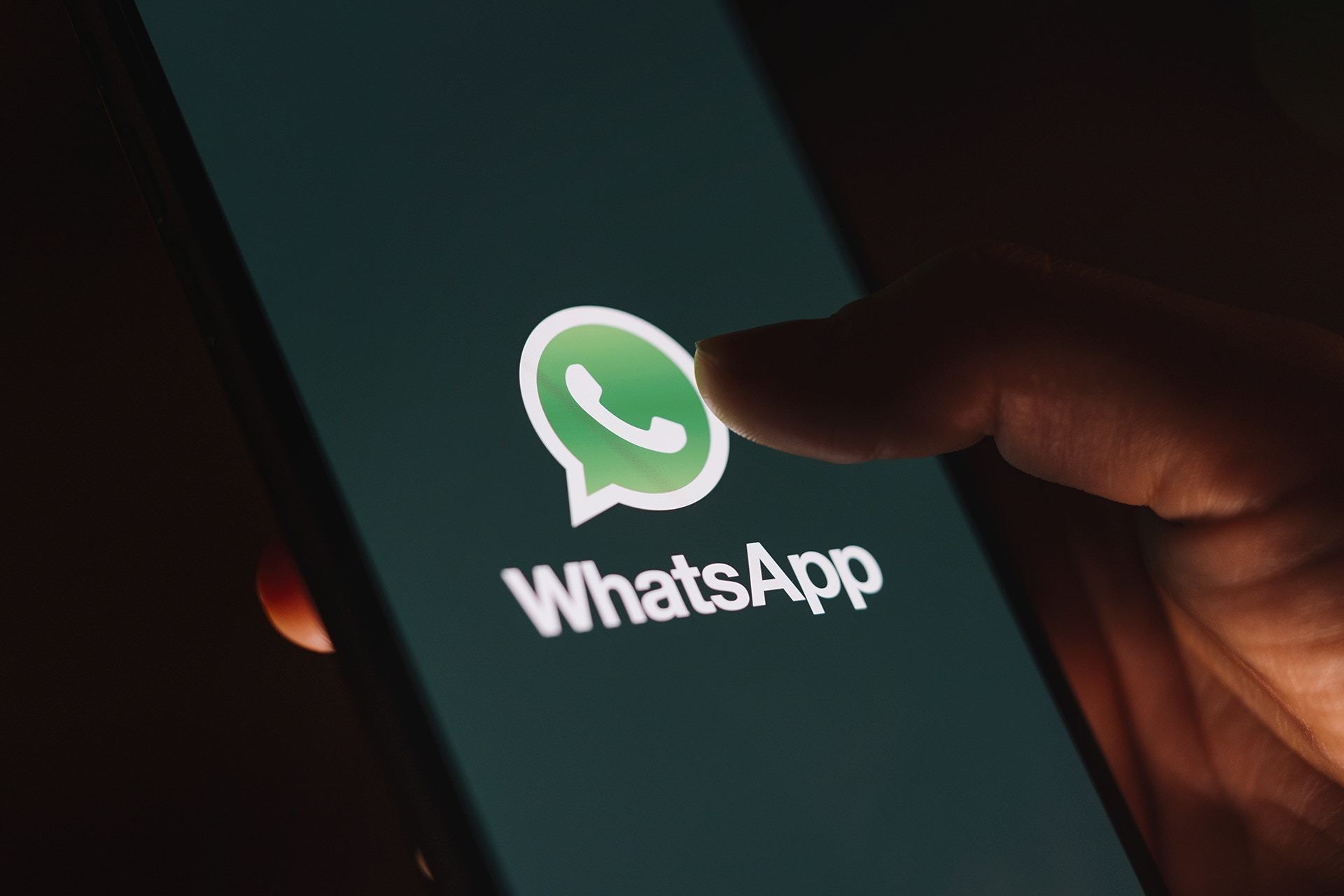 A person holding a cell phone with the WhatsApp logo displayed on screen. This image is being used as the thumbnail for a blog on WhatsApp business marketing