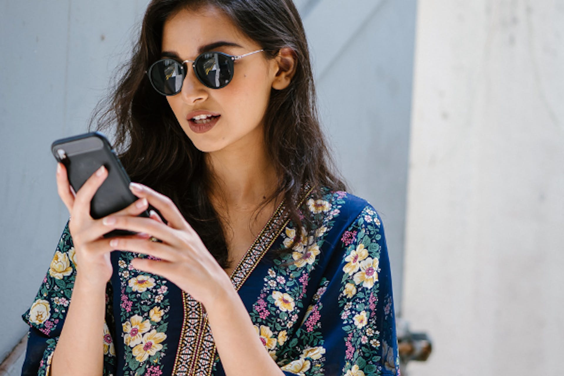 A woman in a colourful floral jacket playing on her phone.