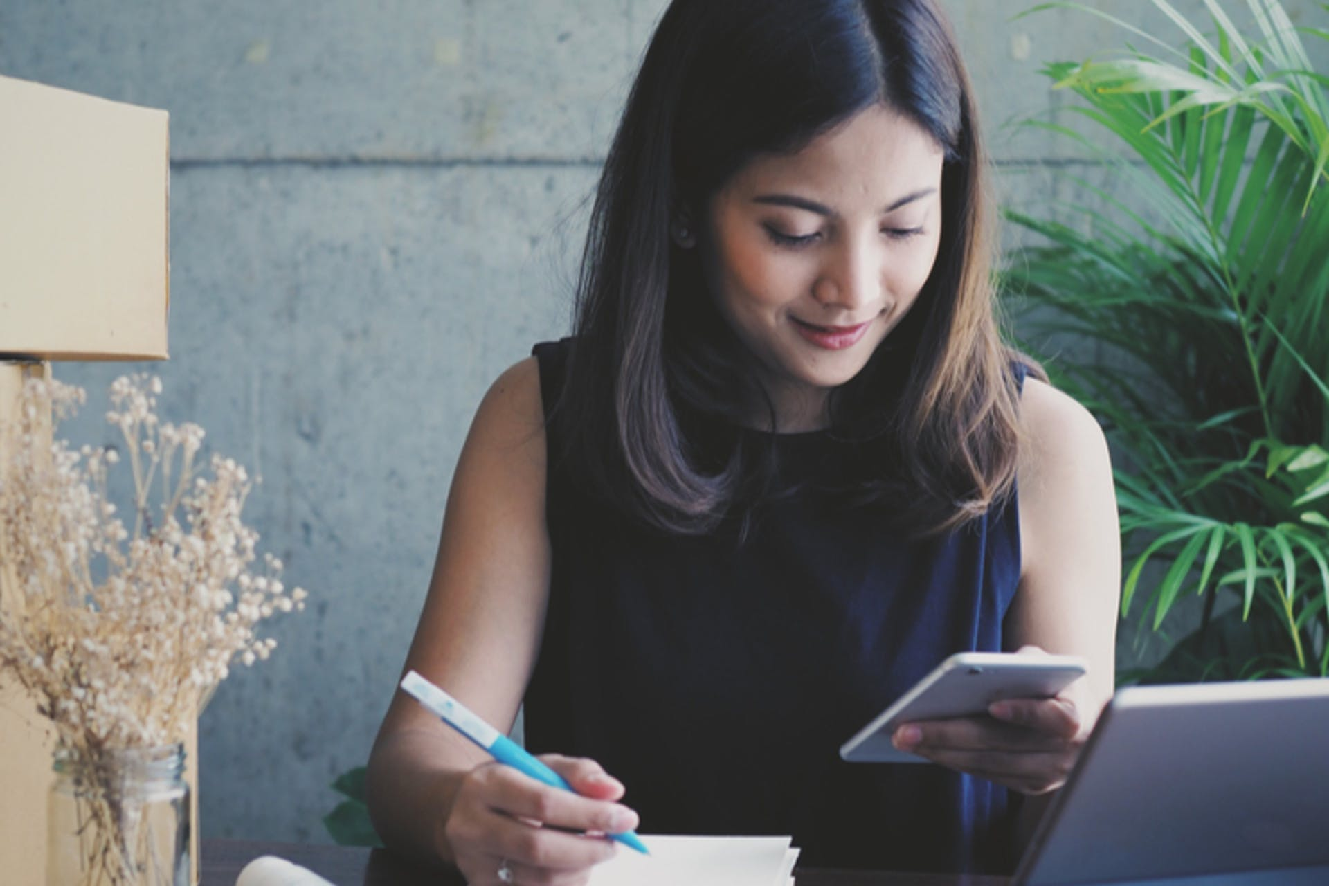 Frau schaut auf Smartphone im Büro