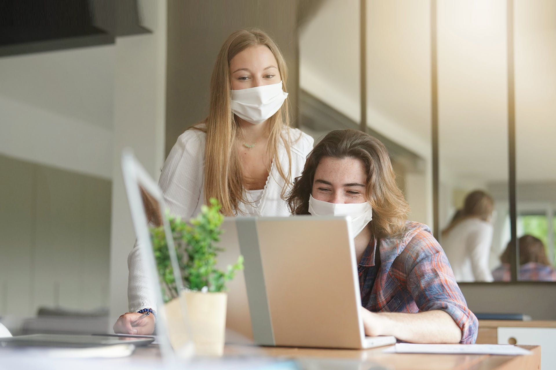 Two people in face masks looking at a laptop screen