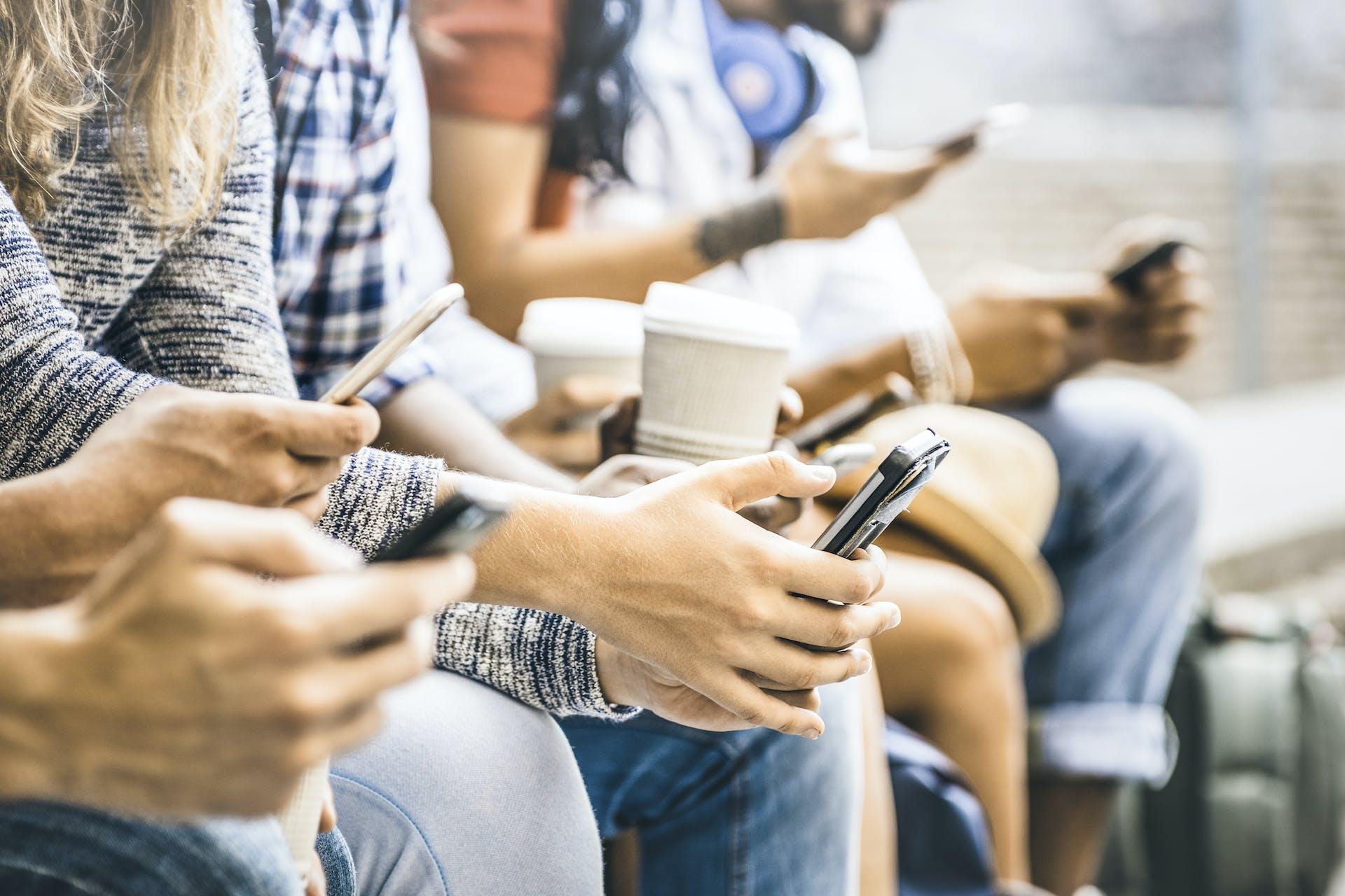 Photo Menschen mit Kaffees und Smartphones in den Händen