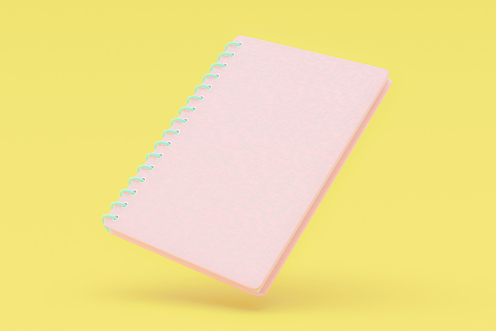 Light pink notebook on yellow background. 10 steps to writing a communication plan blog post