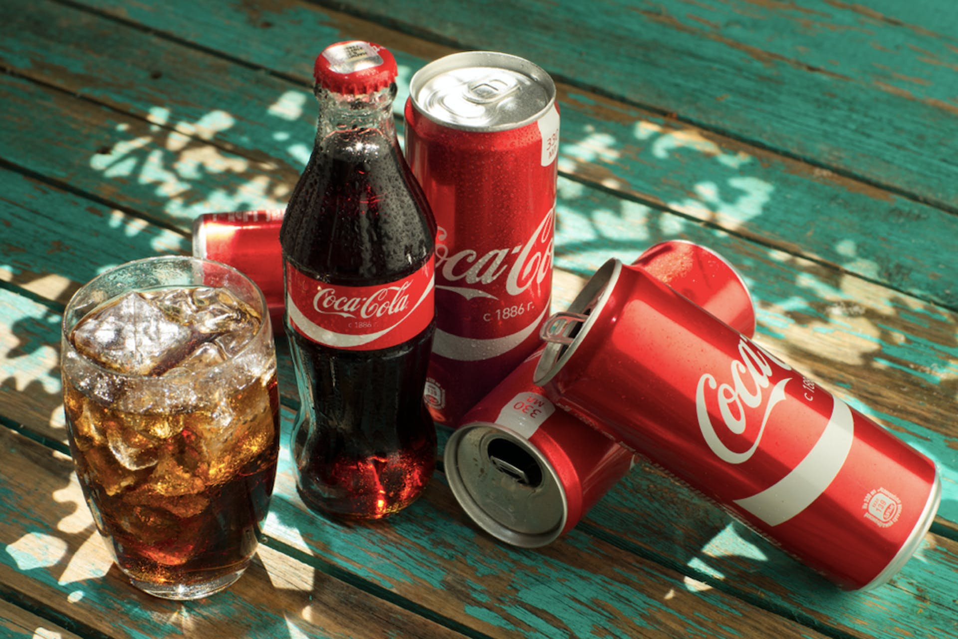 coca-cola can and glass bottle on a wooden table and glass with ice