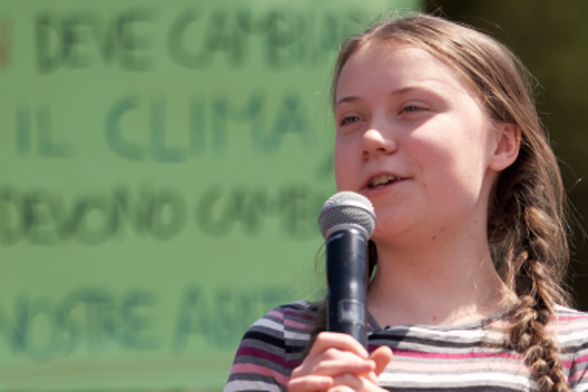 Greta Thunberg speaks through a microphone against the backdrop of a green sign