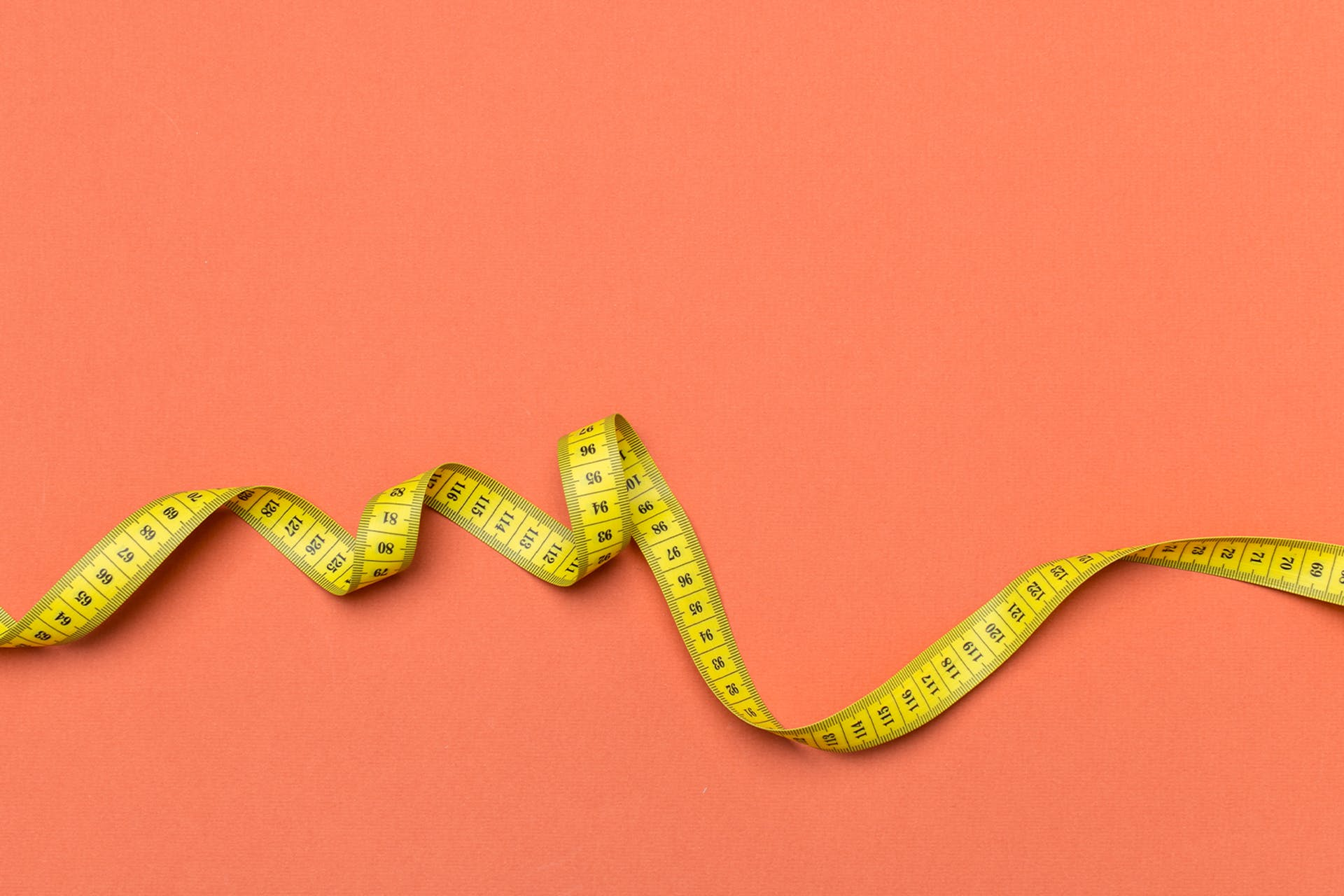 yellow tape measure against a coral pink background