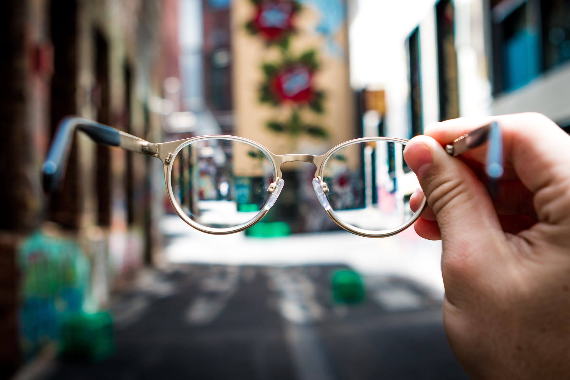 Person holding eyeglasses up to a brightly lit street. Header image for 10 steps for a social media audit.