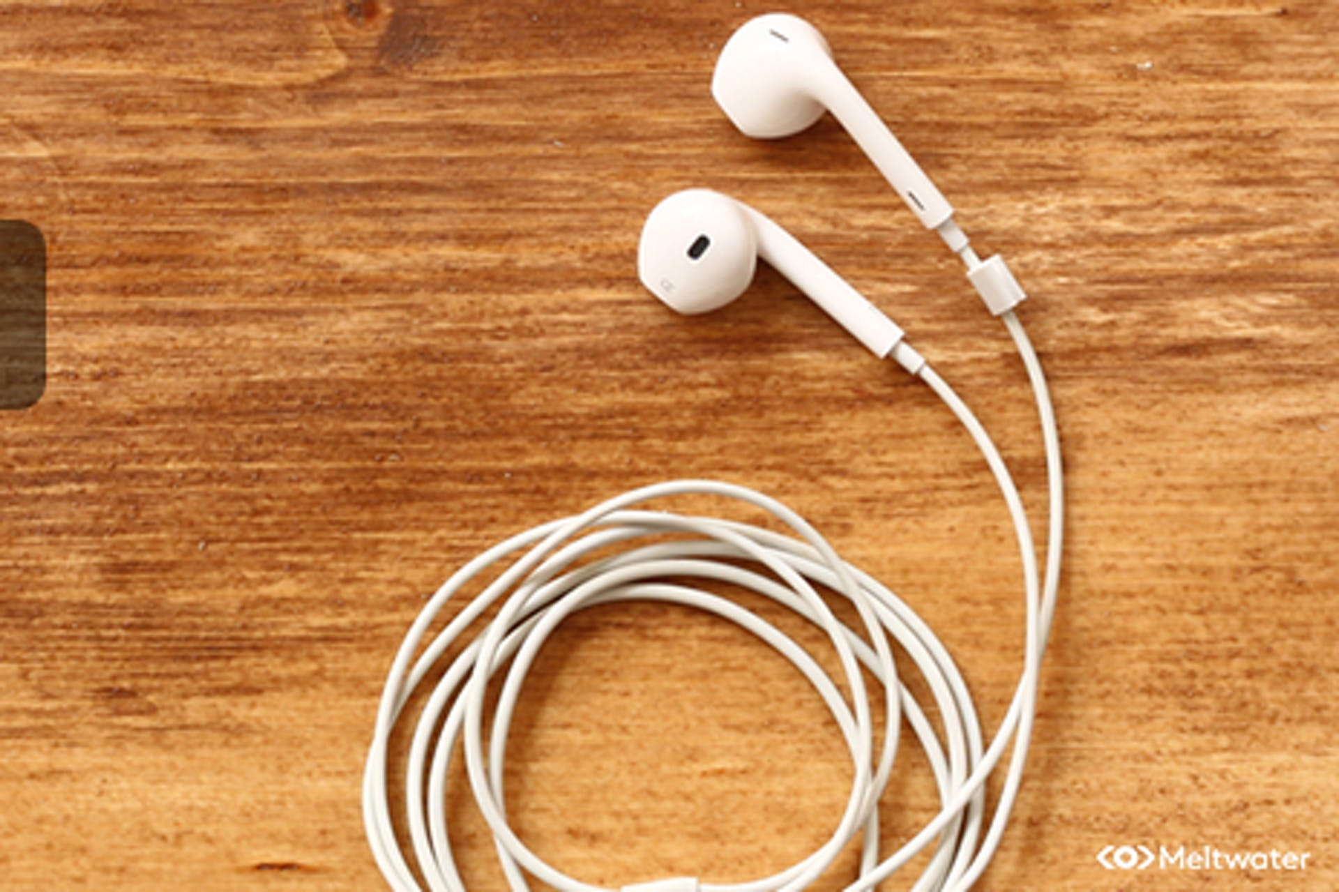 Apple Inear Kopfhörer auf Holztisch Meltwater Social Listening