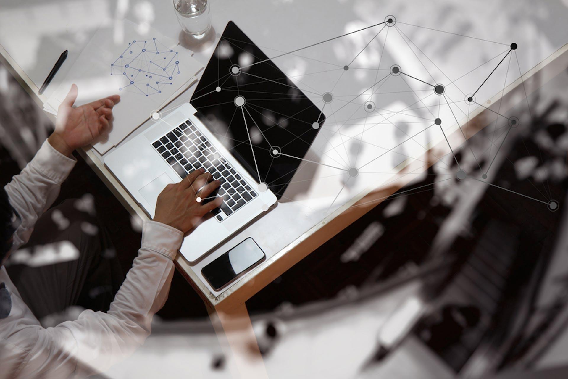 Ein Mann arbeitet am Laptop mit analytischen Elementen - eventuell führt er gerade eine Branchenstrukturanalyse nach Porter durch.