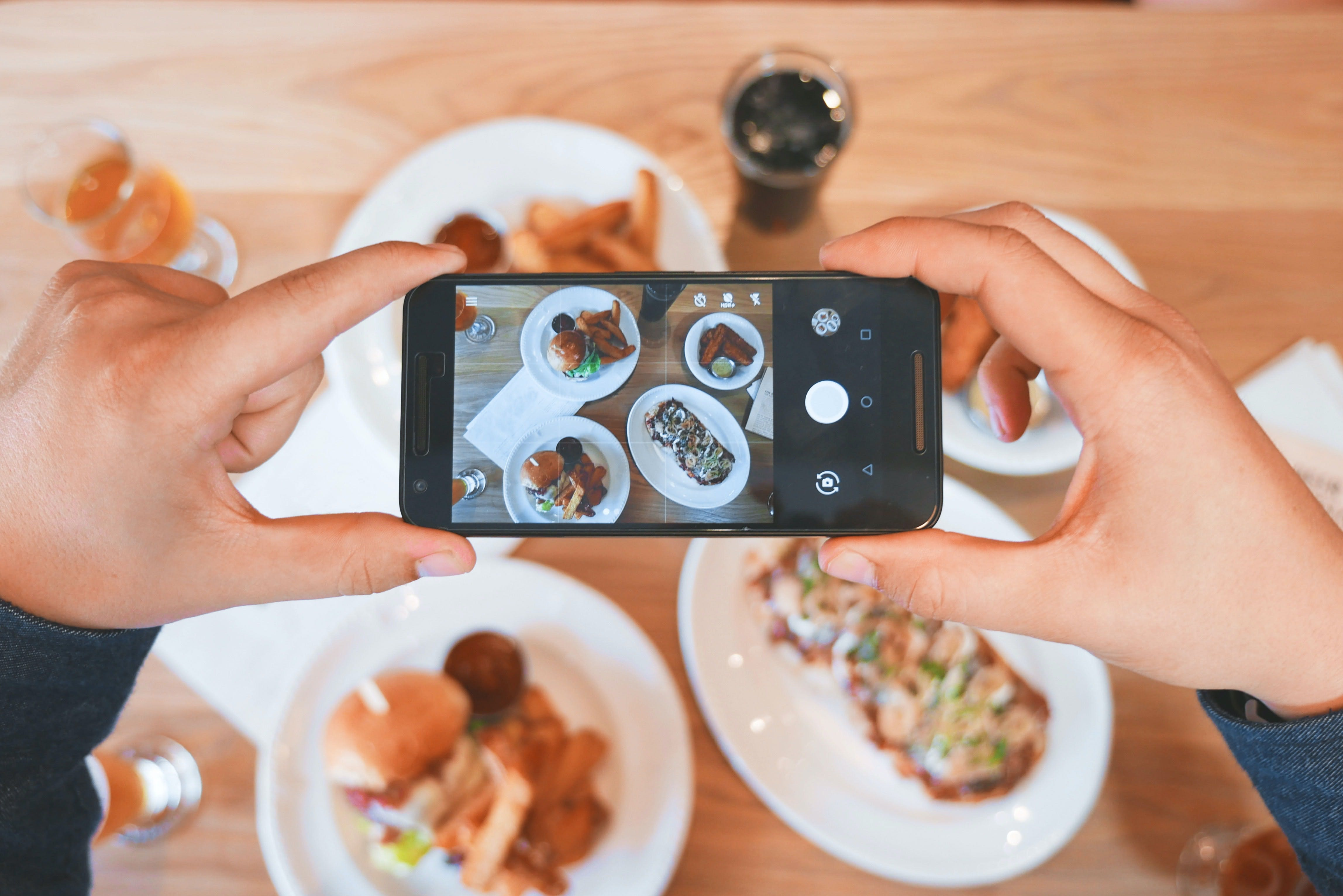 person holding a phone from above and taking a photo of food on the table