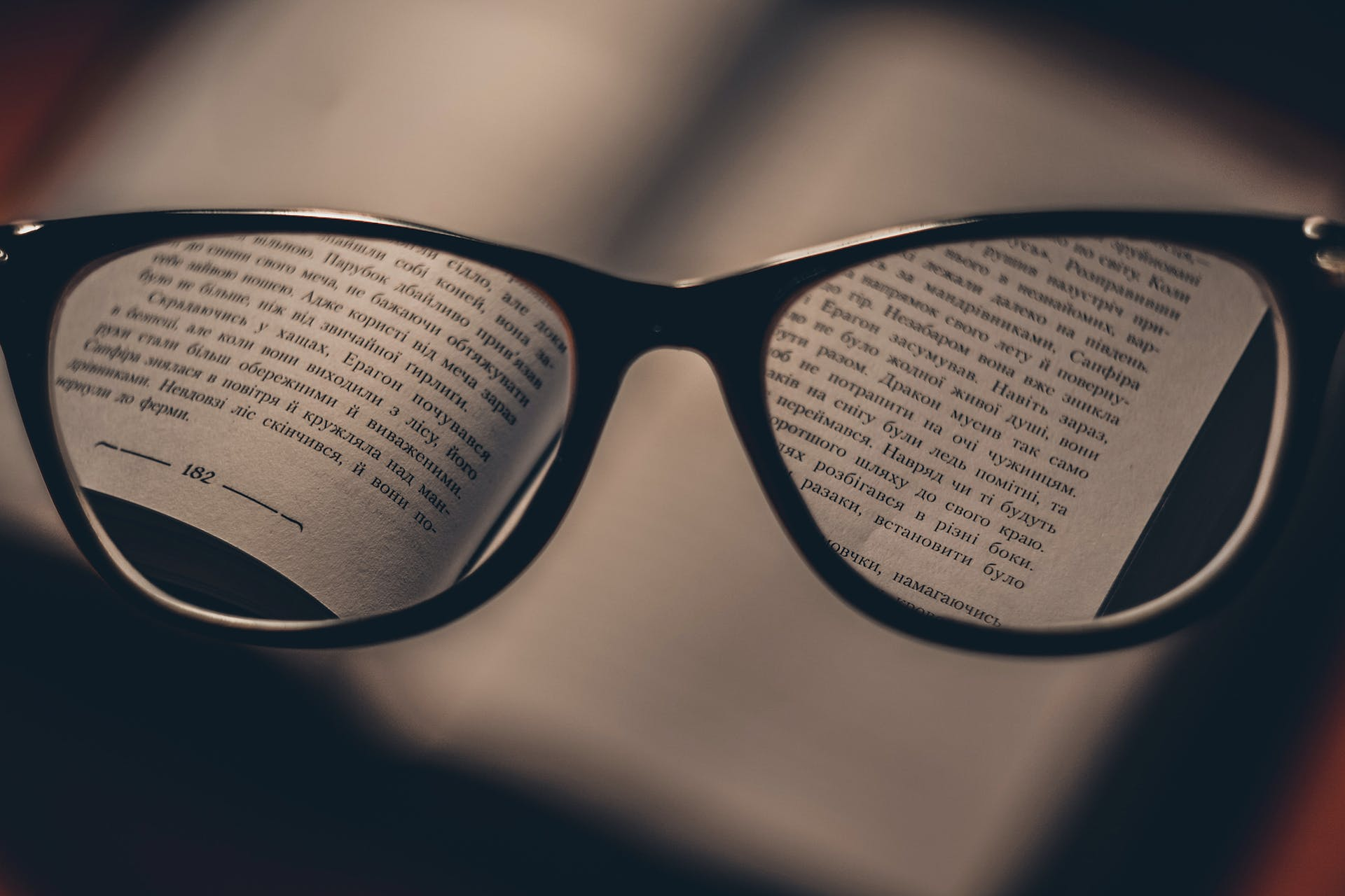 photo of a glasses held in front of an open book
