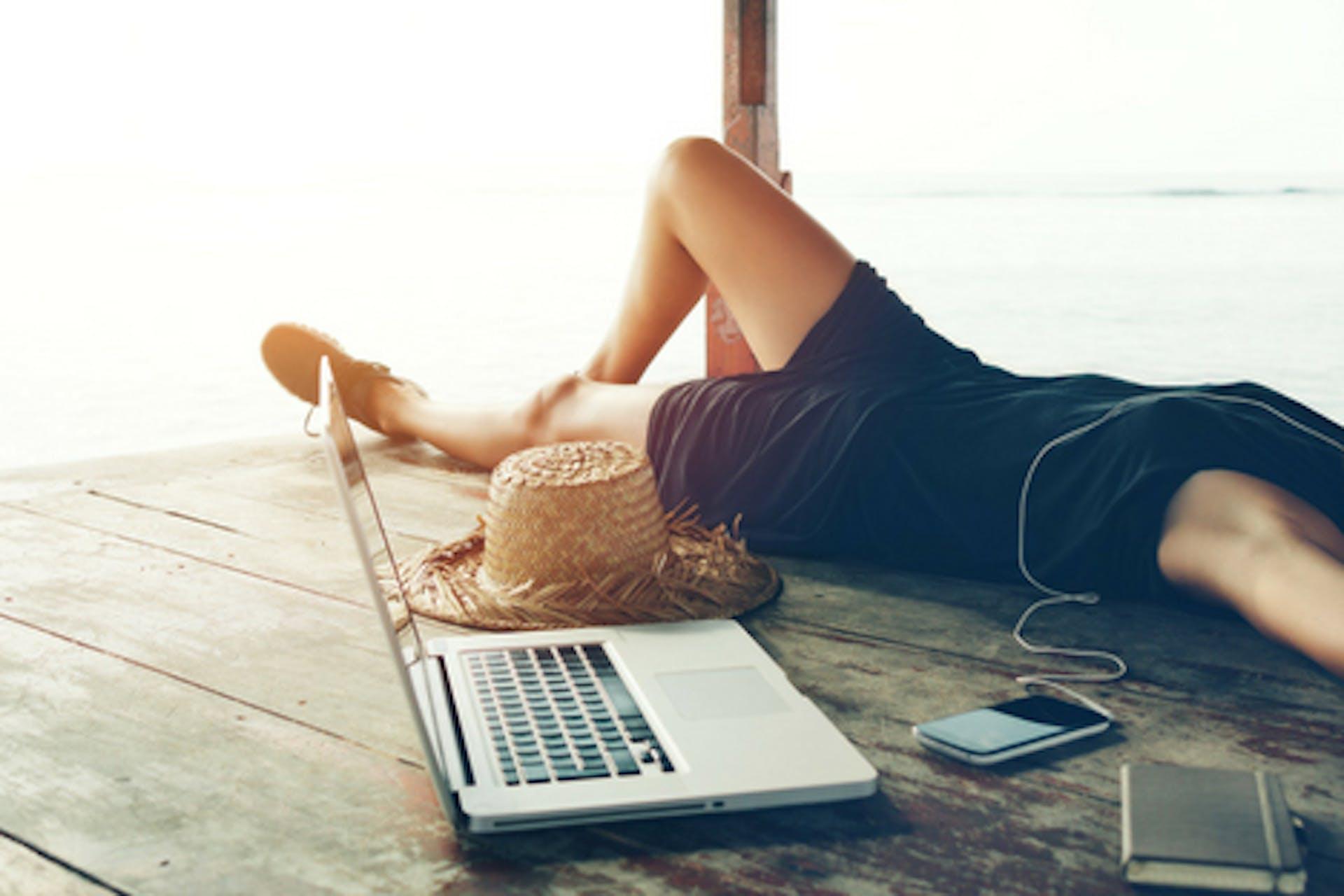 Frau liegt mit Kopfhörern, Smartphone und Laptop auf einem Steg auf dem Wasser