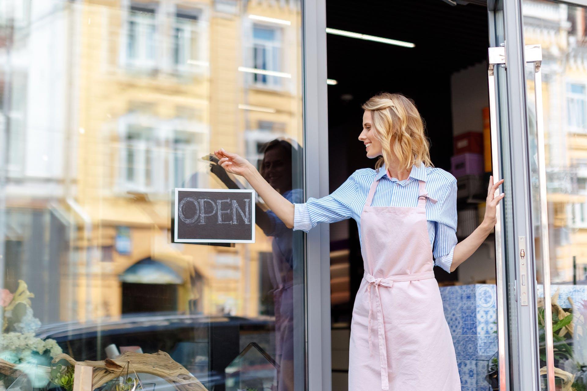 Femme ouvrant la porte d'un magasin pour illustrer le marketing offline