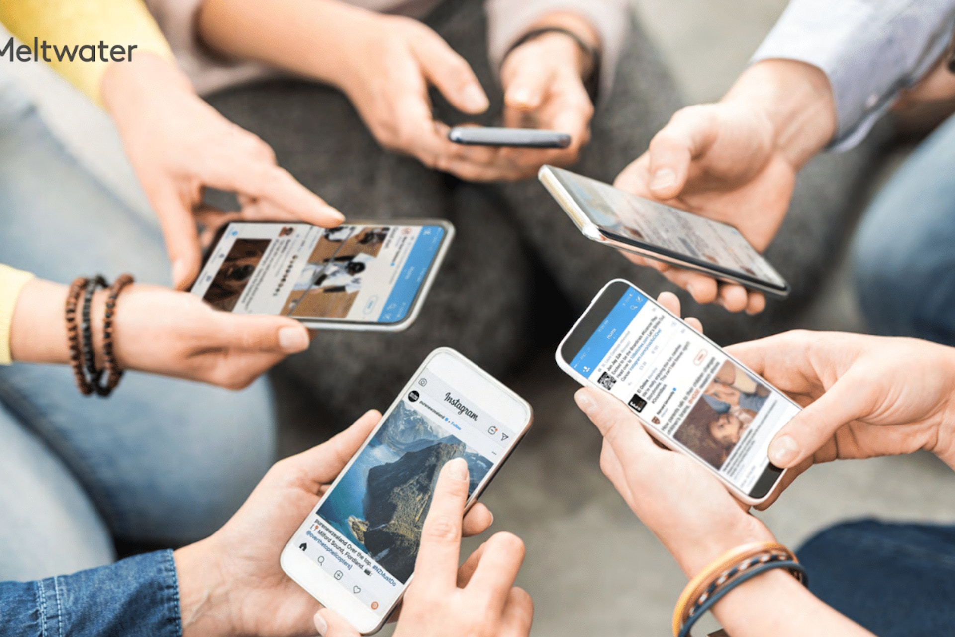 people holding up their smartphones with social media in a circle