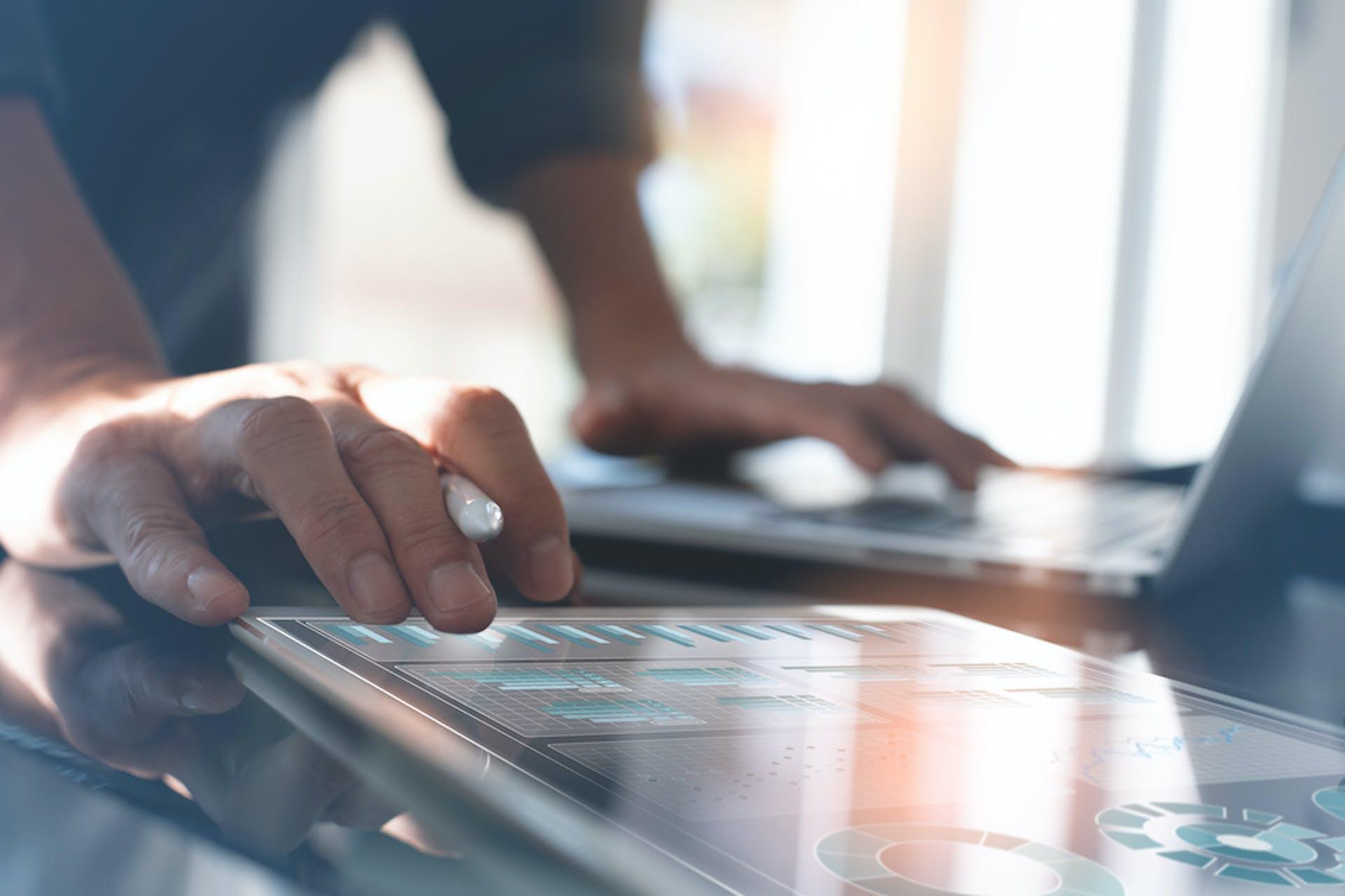 Nahaufnahme der Hände eines Mannes, der mit einem Tablet mit Social Media KPI Analysen arbeitet