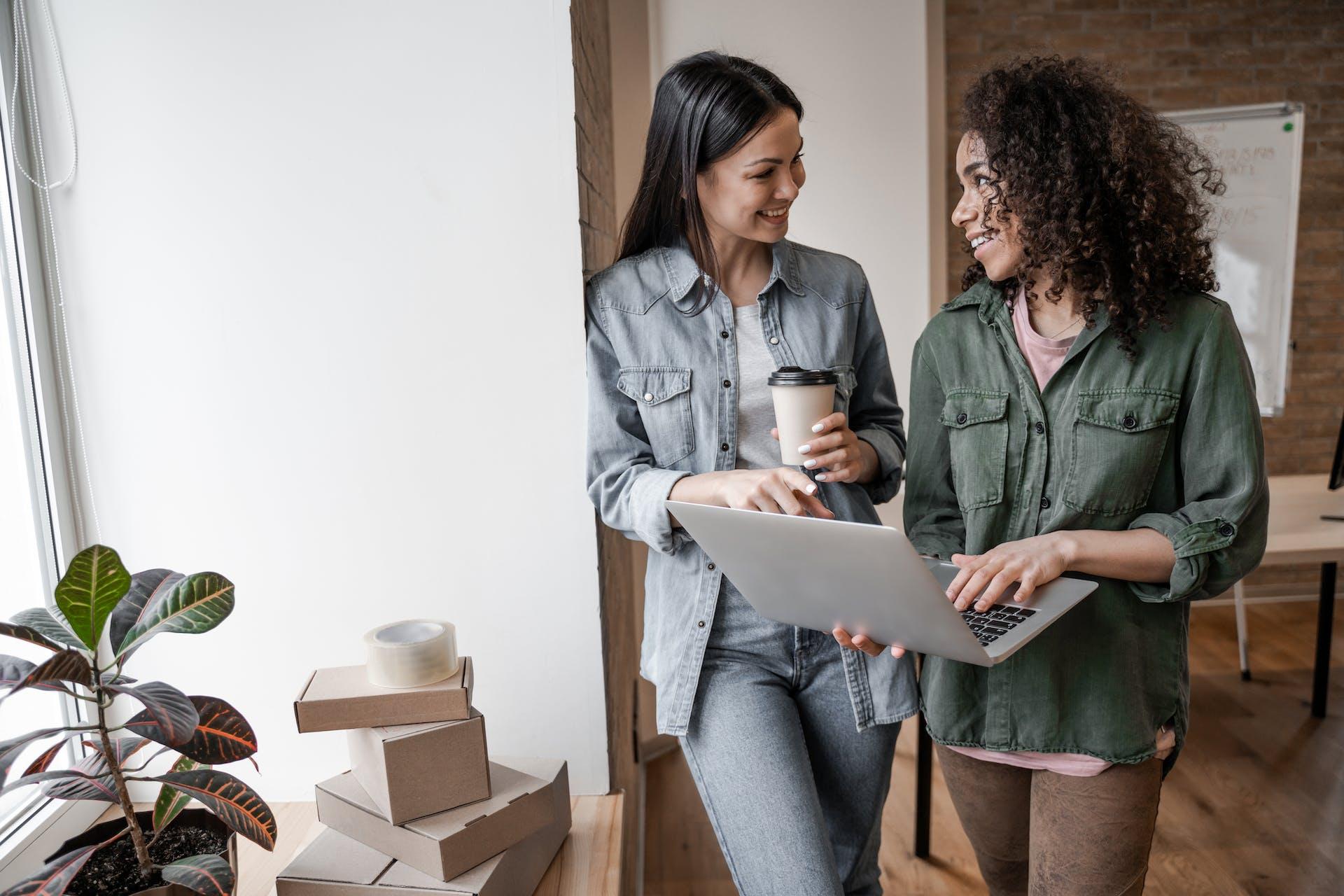 Deux femmes qui tiennent un ordinateur et un café en discutant de marketing B2B