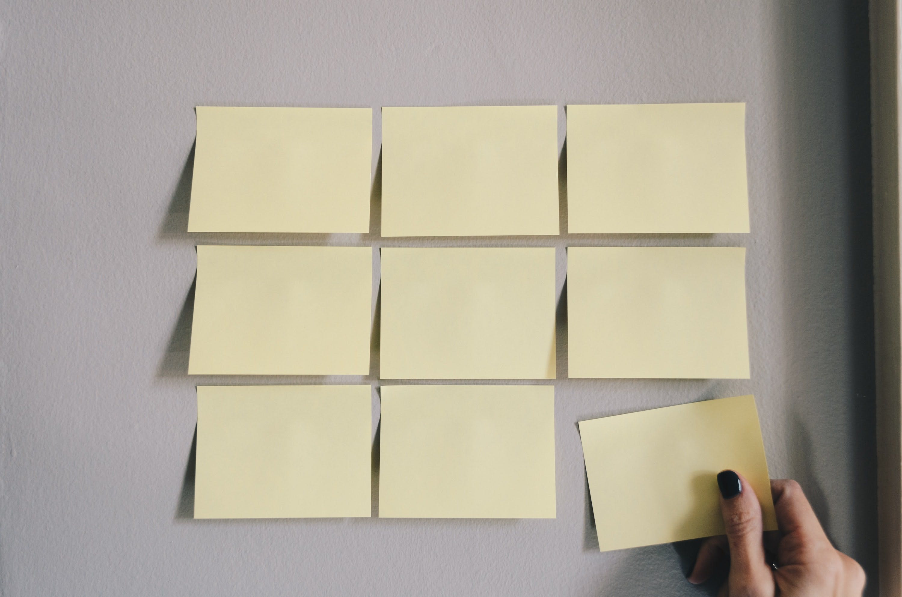 Grid of blank sticky notes with woman's hand adding final sticky note to the bottom row.