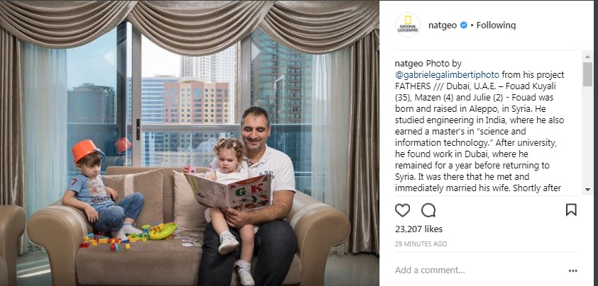An Instagram post from National Geogrpahic featuring a father reading to his duaghter on the couch