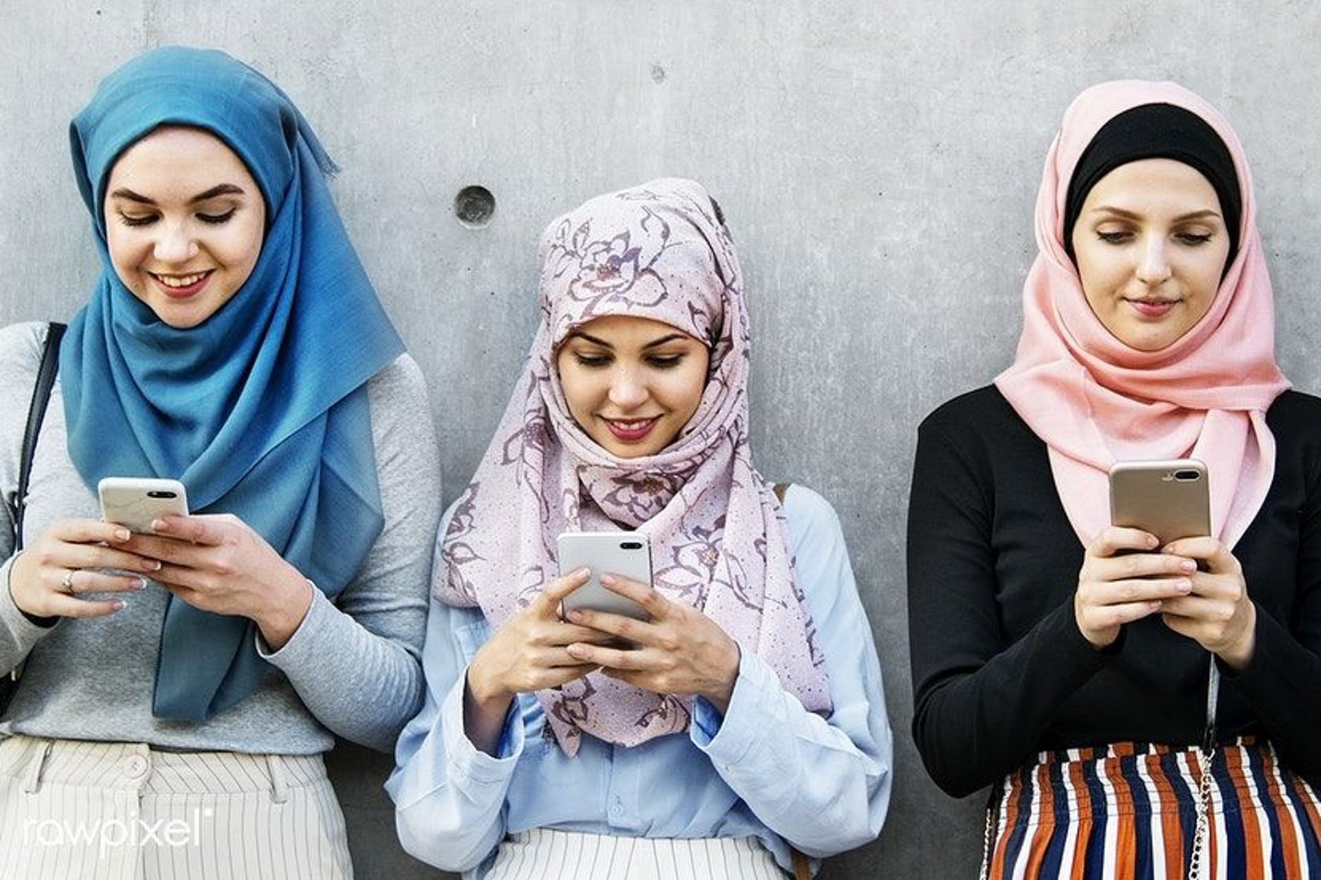four arab women against a grey wall looking at their smartphones