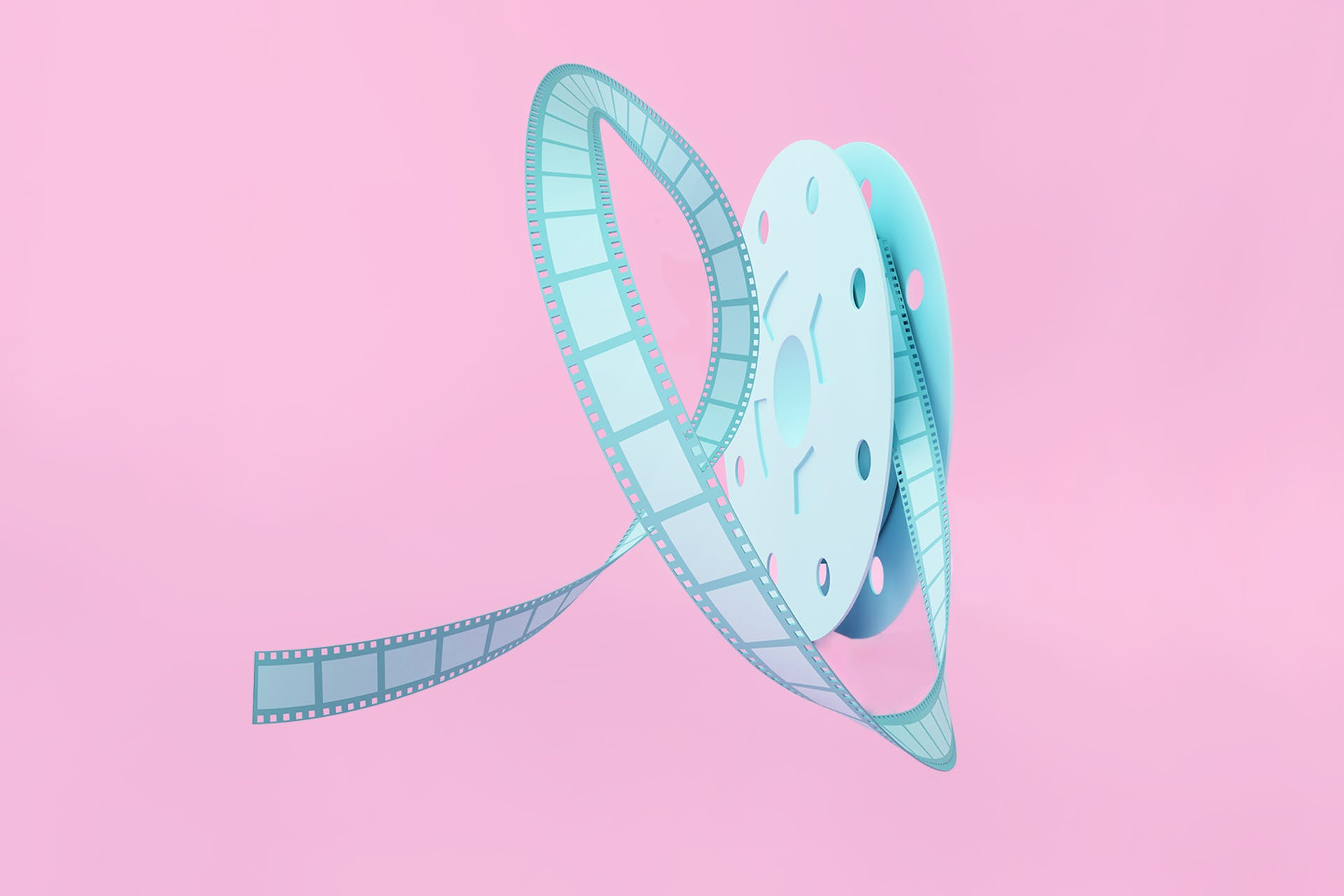 Image of a light blue old-fashioned film reel with film coming out, on a pink background. How to create and use Instagram Reels blog post