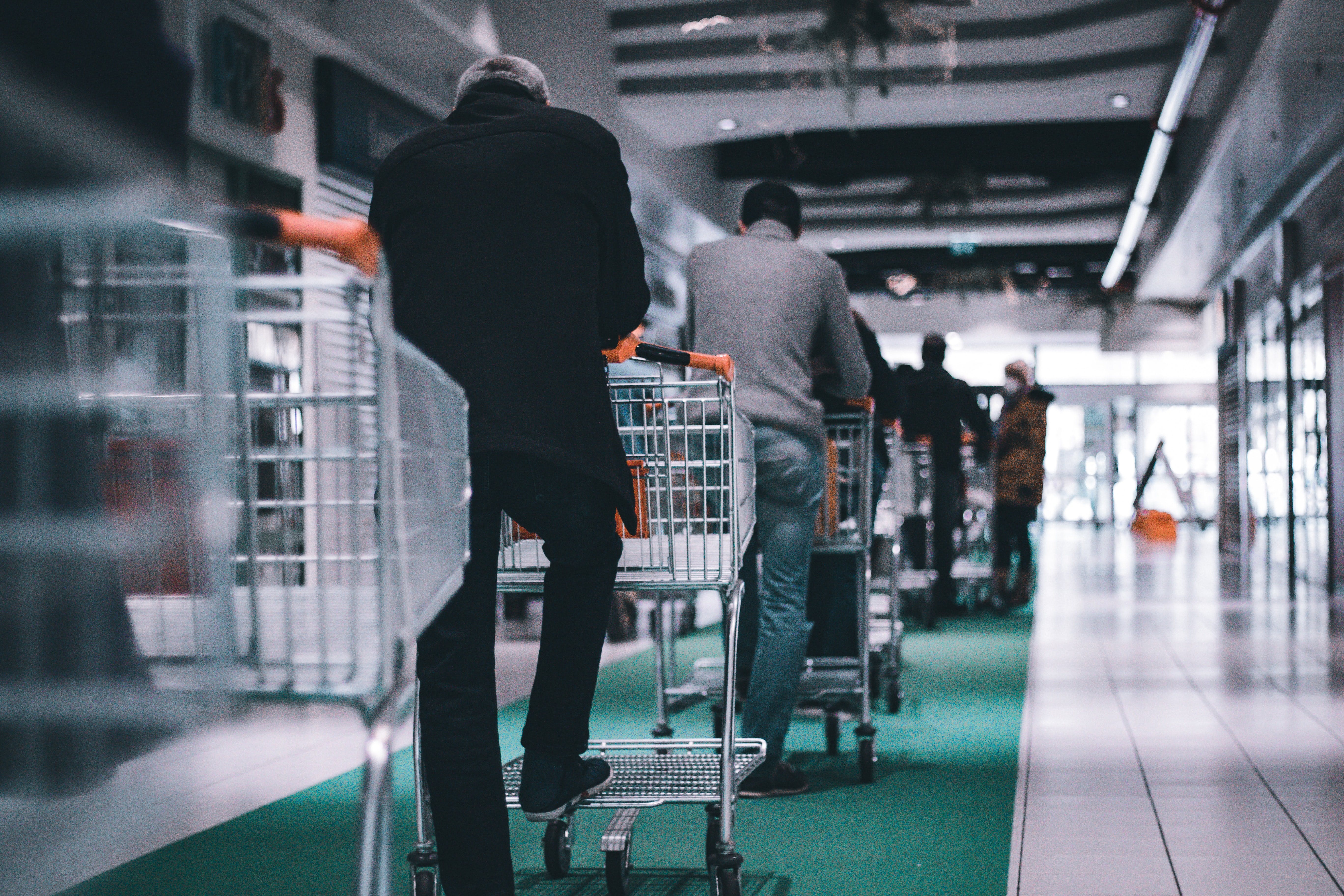 man in black long sleeve shirt standing in queue with a shopping cart