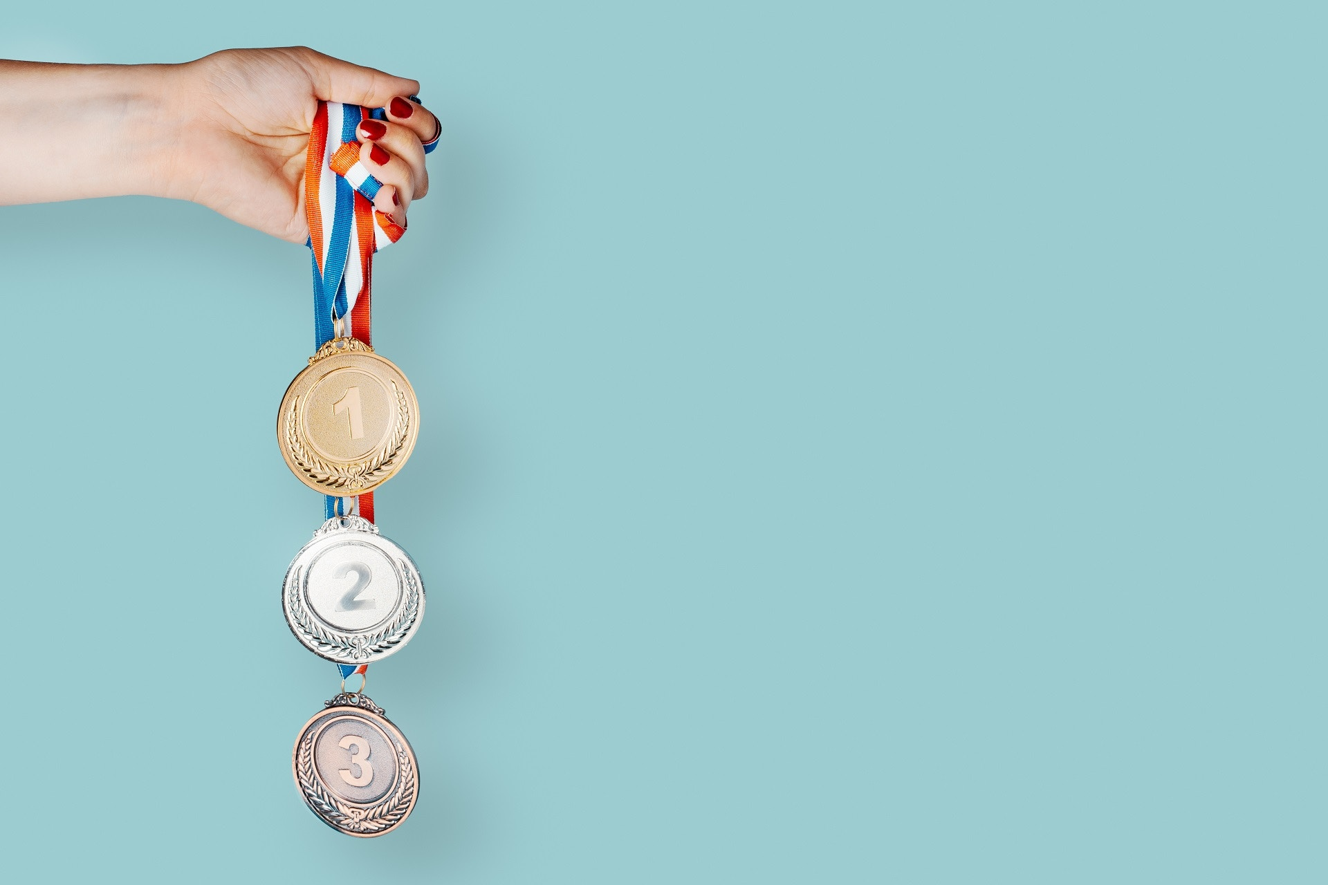 Hand holding medals on blue background