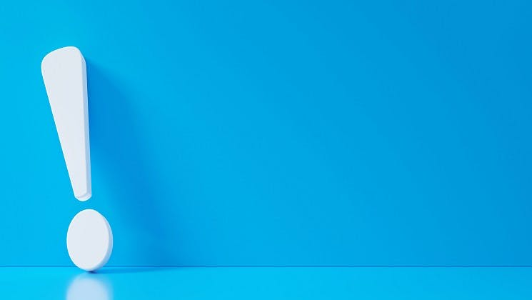 A white exclamation point on blue background