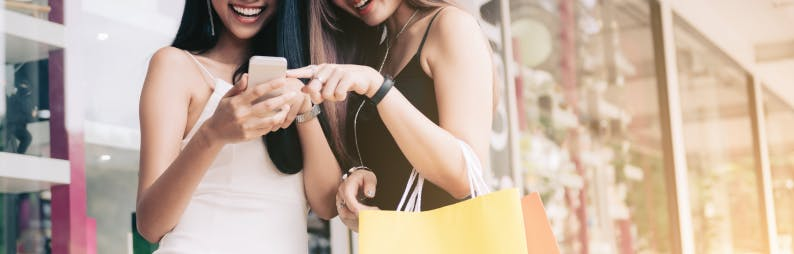 two girls with shopping bags and a cell phone in hand looking at the screen while smiling