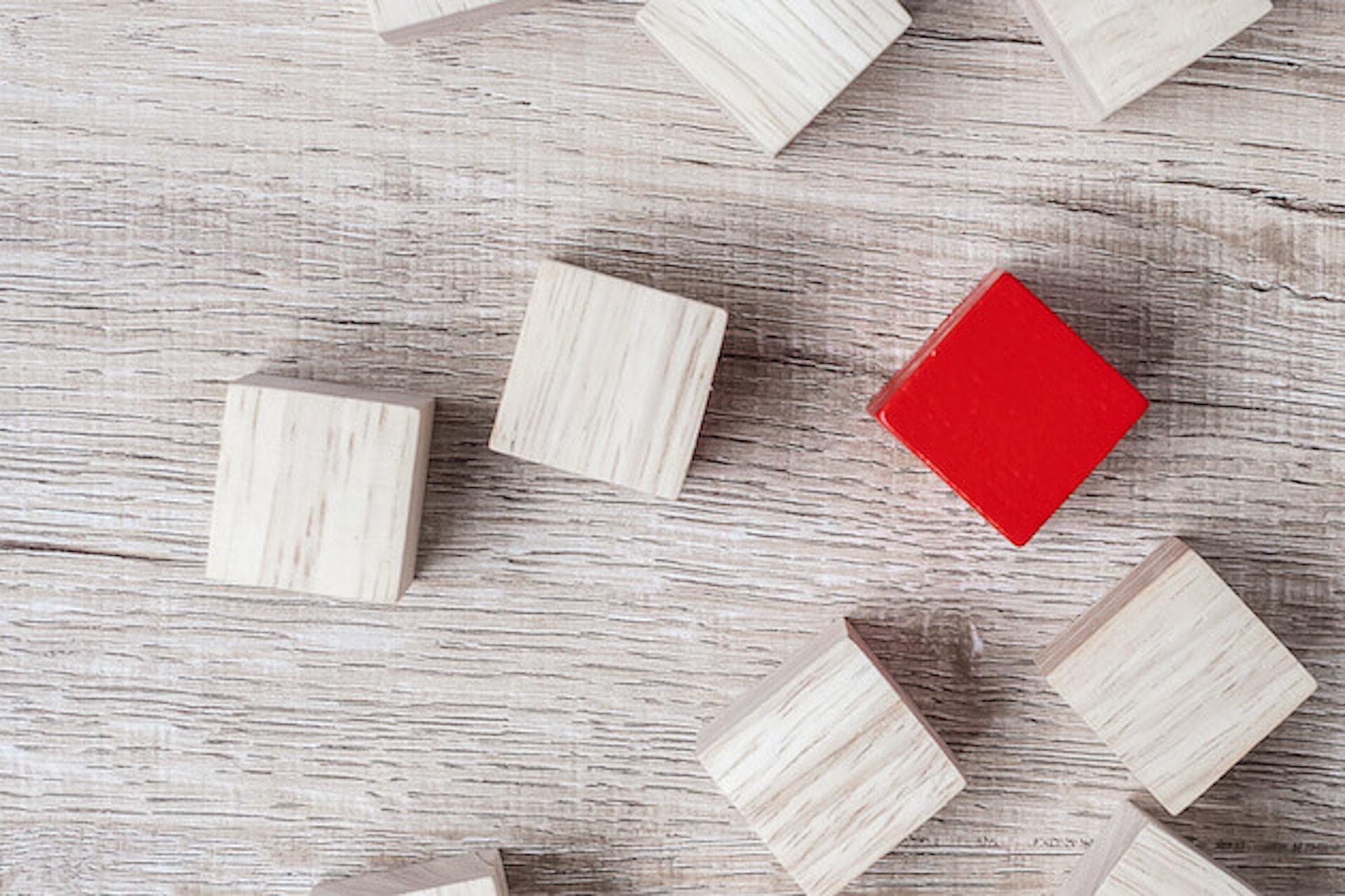 Man sieht einen weiß gestrichenen Holztisch, auf dem viele weiße Holzwürfel zu sehen sind. In der Mitte sticht ein roter Würfel hervor. Dieses Bild ist das Titelbild unseres Beitrags zur Erarbeitung eines USPs / Alleinstellungsmerkmals.
