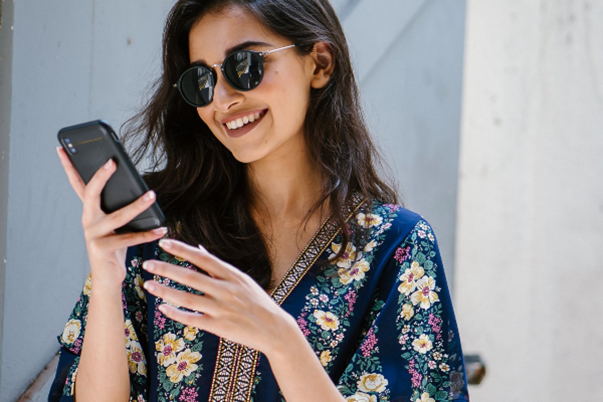 woman looking at her phone smiling