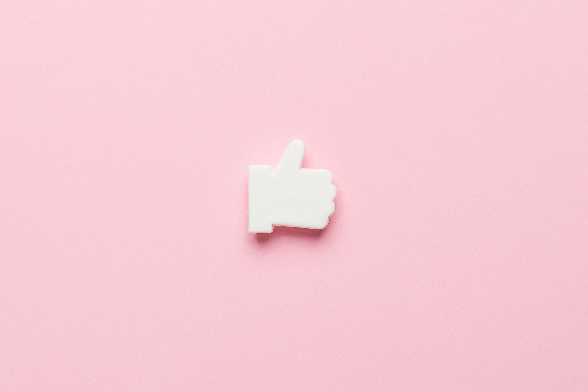 """Facebook thumbs up """"like"""" icon on pink background. Blog post: how to get more likes on your business Facebook page"""