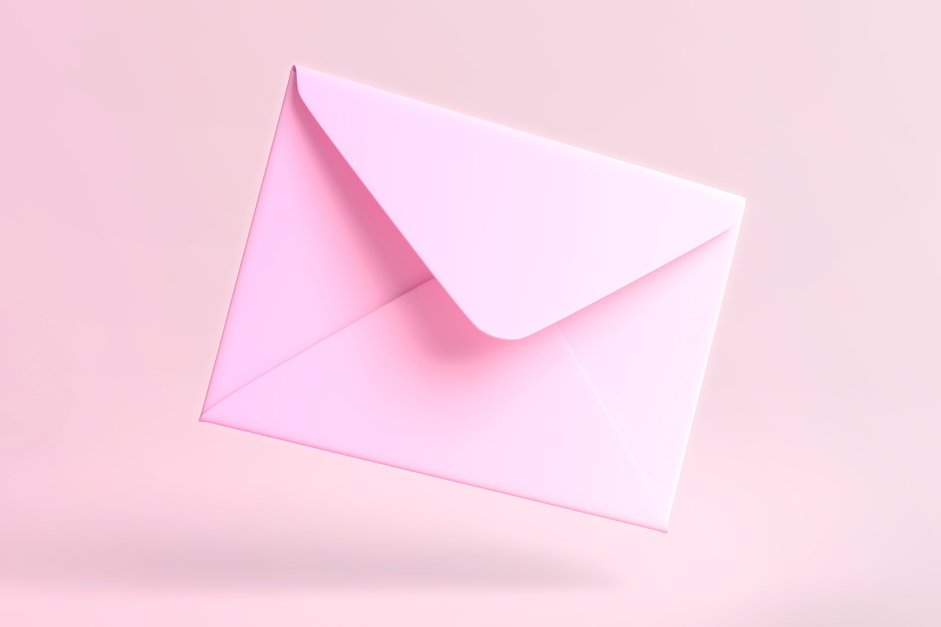 Slightly open pink envelope on light pink background. Header image for blog post: why you need an internal newsletter