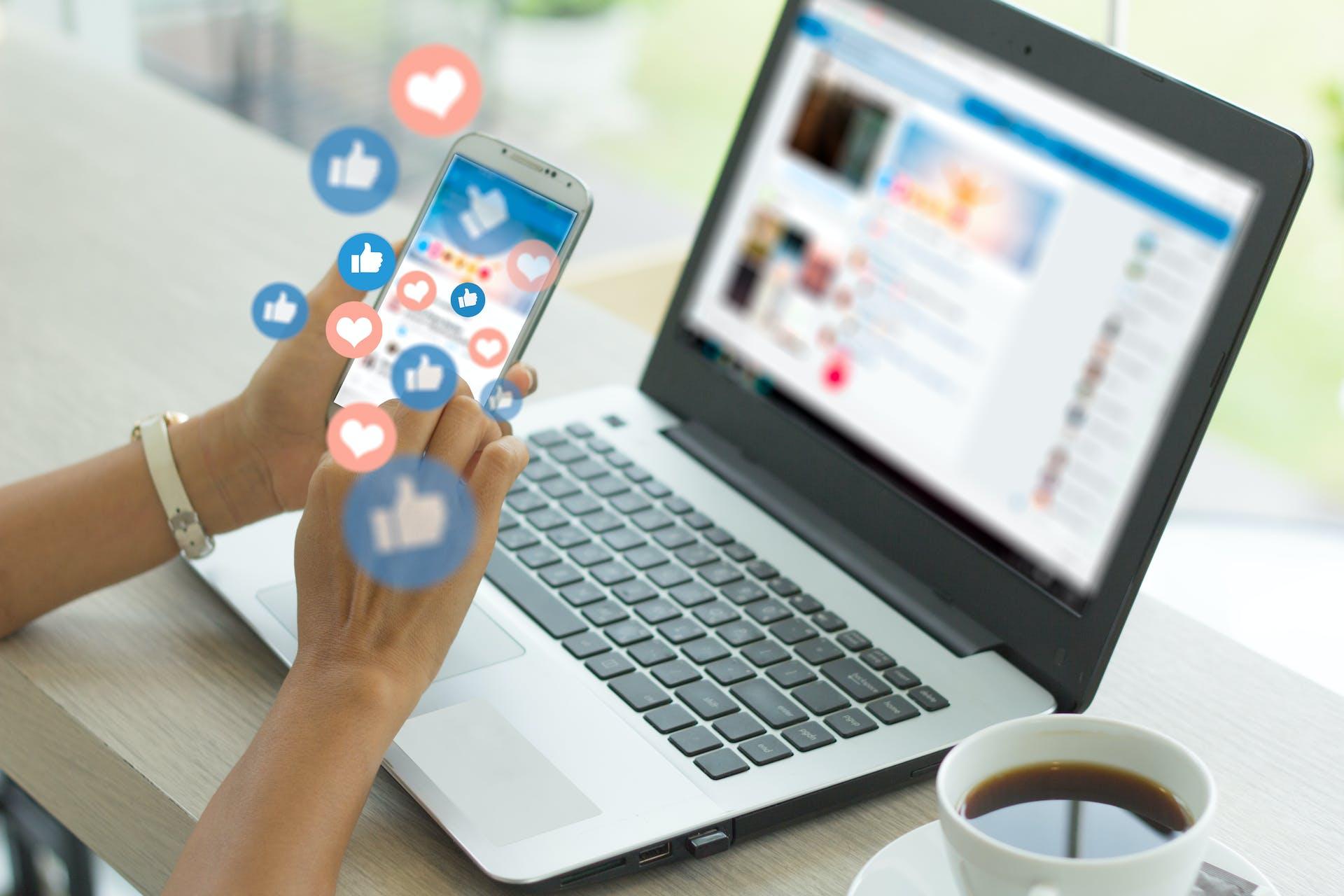 Smartphone vor Laptop, aus dem Likes und Love Icons fliegen