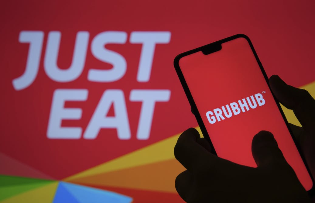 A hand holding a phone with the GrubHub app up, in front of a Just Eat sign