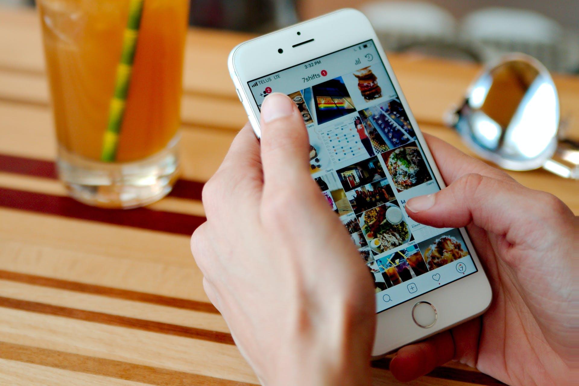 Foto von weiblichen Händen, die ein weißes Smartphone halten, bei dem der Instagram Feed offen ist