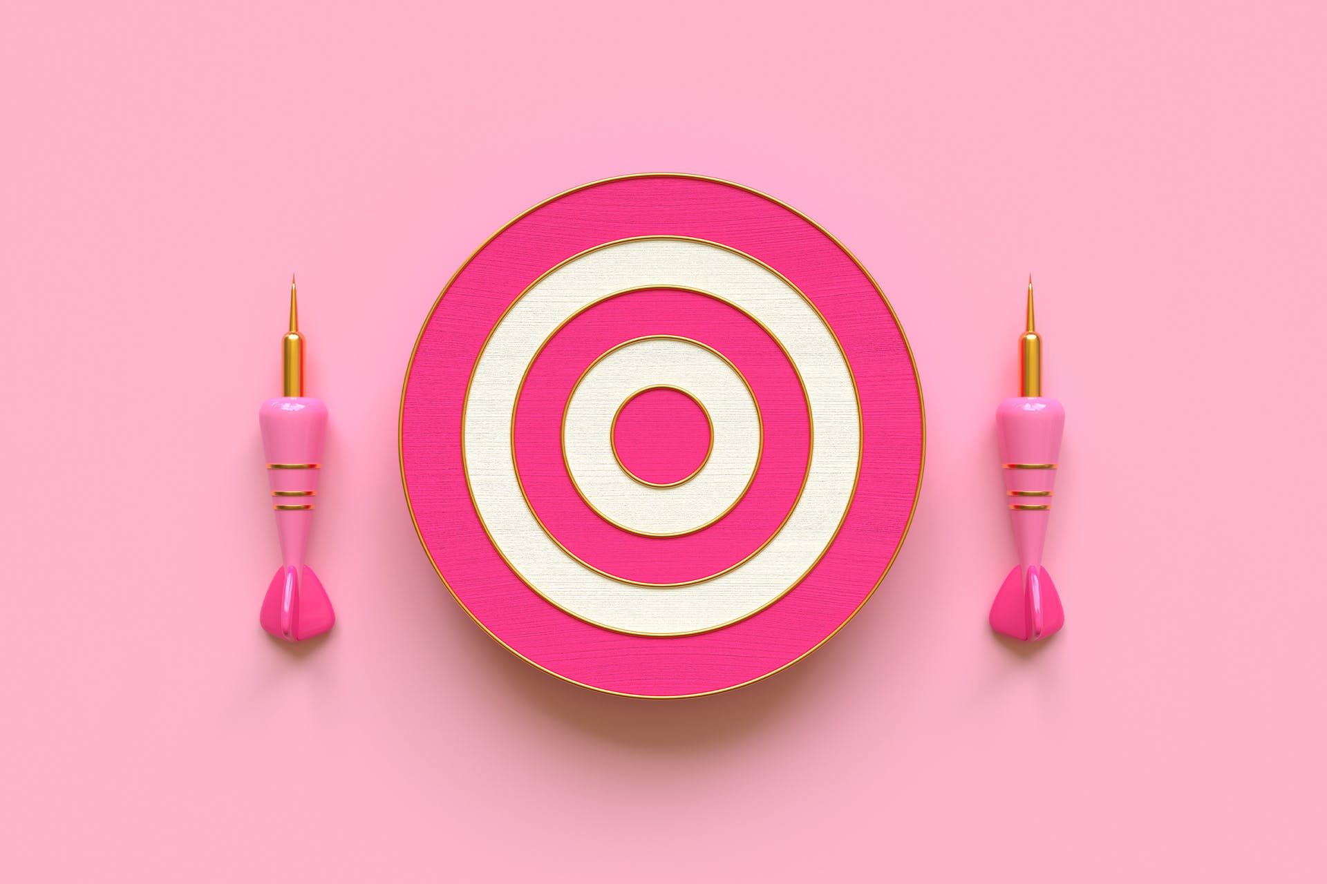 A bullseye dartboard with two pink darts next to it.