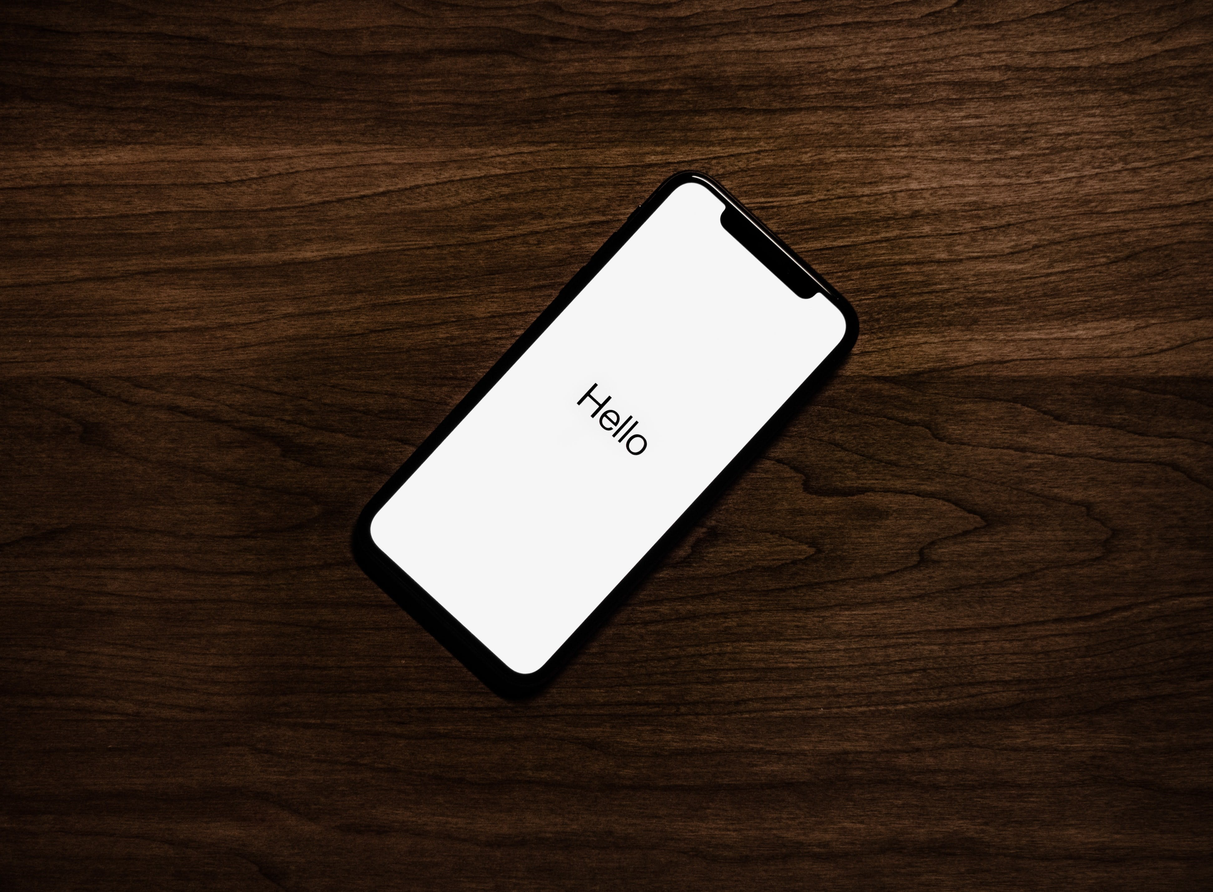 apple iphone on wooden desk with hello on the screen