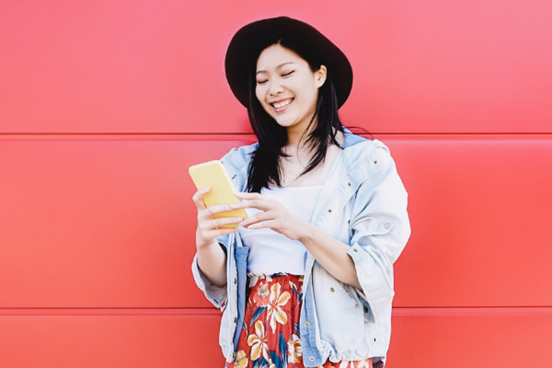 asian woman with smartphone influencer in front of red wall
