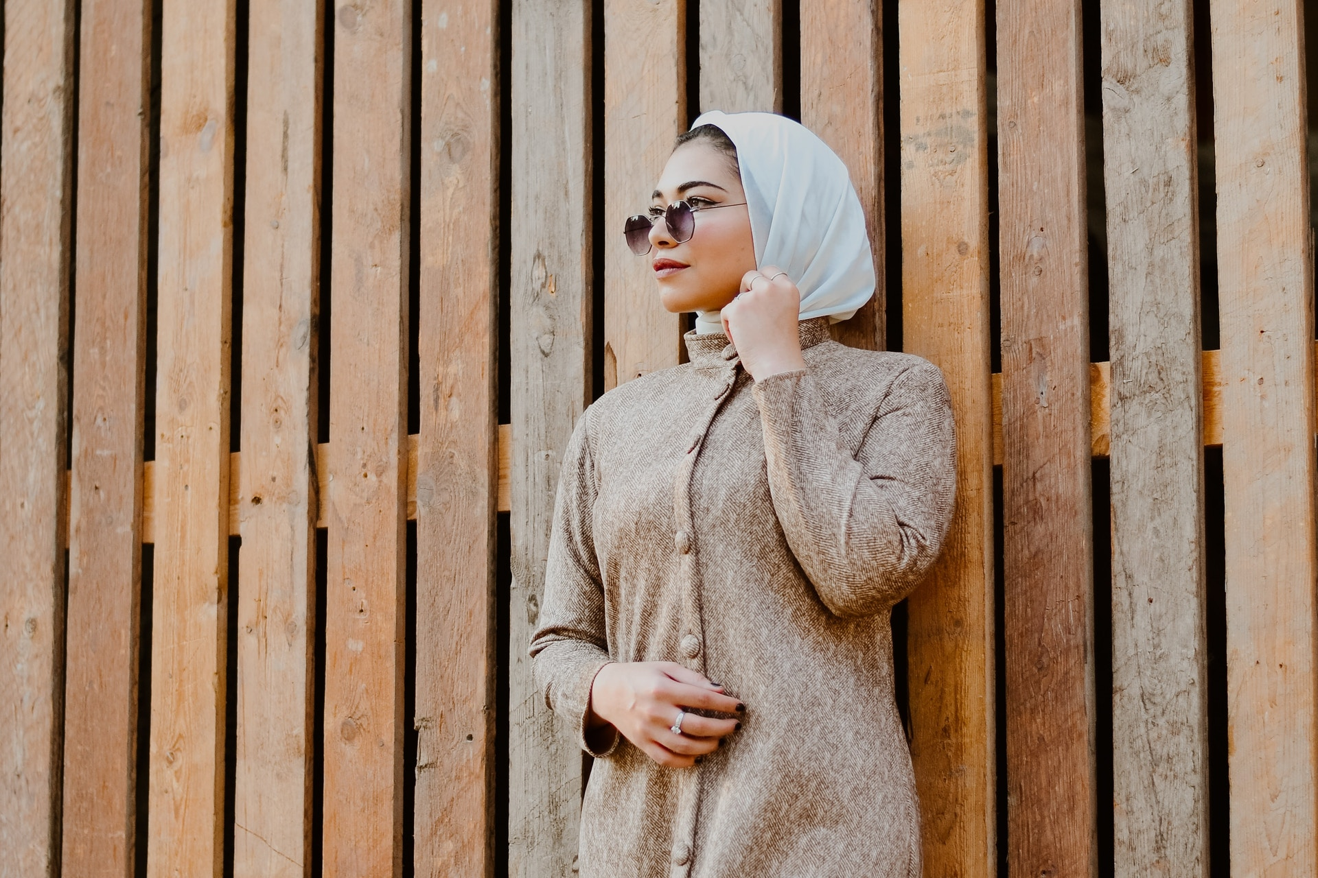 arab woman wearing sunglasses standing against wooden wall