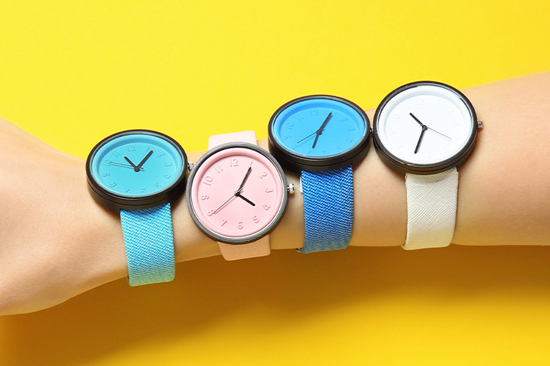 Person wearing multiple watches for different time zones on bright yellow background. Hero image for social media management blog post.