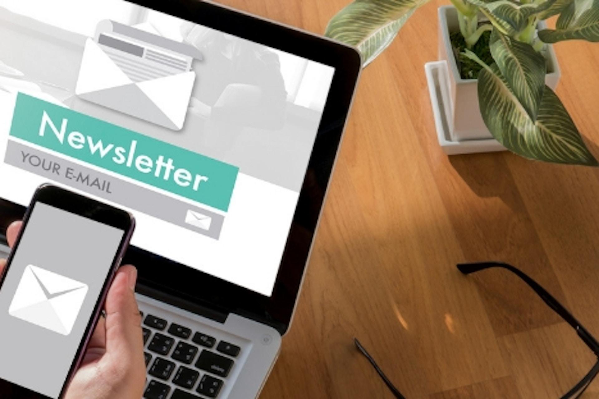 Foto Laptop und Smartphone auf Tisch mit Newsletter Screen Icons